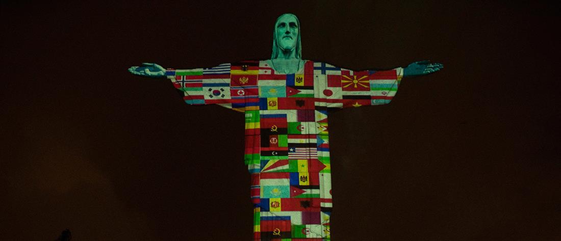 """Το άγαλμα του Χριστού φωτίστηκε με σημαίες χωρών που """"χτύπησε"""" ο κορονοϊός (εικόνες)"""