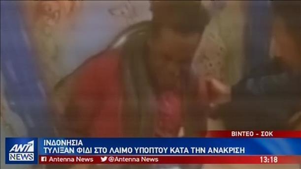 Αστυνομικοί ανακρίνουν ύποπτο τυλίγοντας ένα φίδι στο κεφάλι του